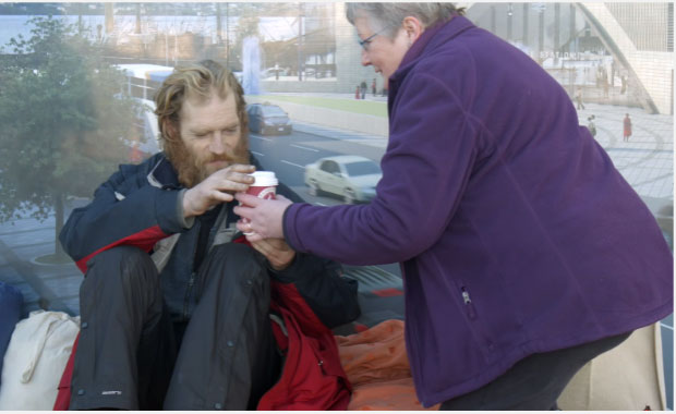 Woman handing coffee to a homeless man
