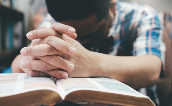 Man's hands on a Bible praying.