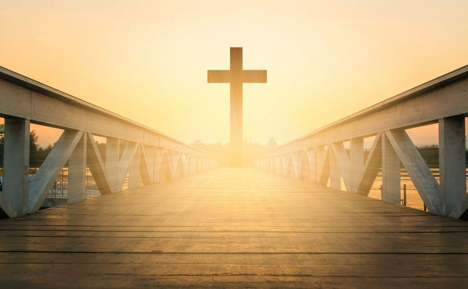 A cross standing at the end of a bridge at golden hour before sunset.