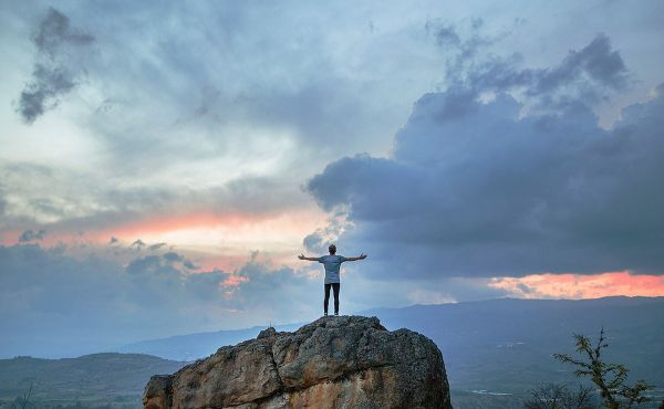 Man standing on mountaintop with arms raised
