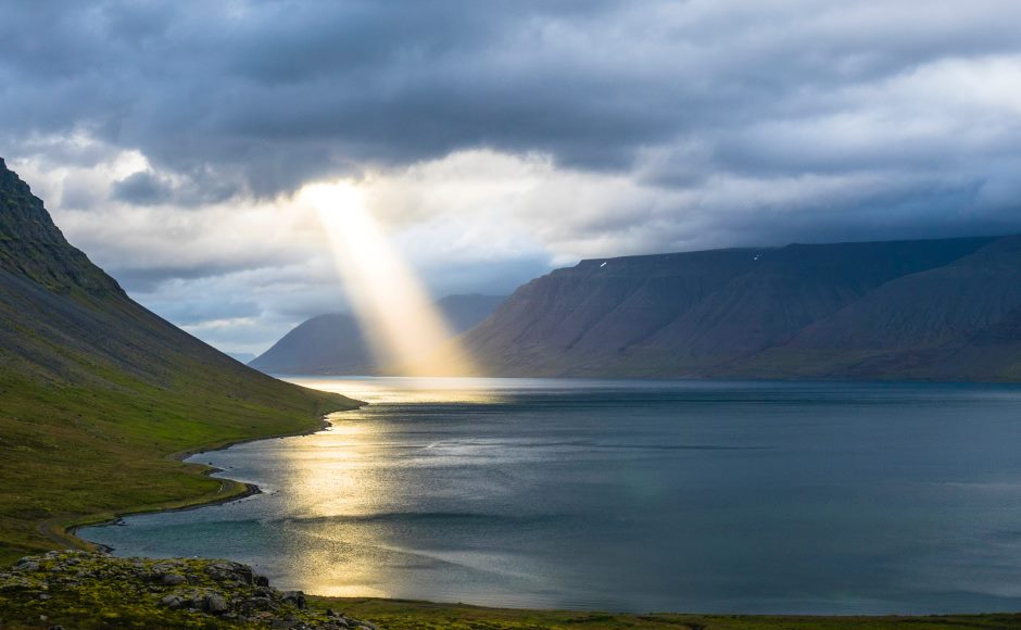 Beam of light shining on loch surrounded by mountains