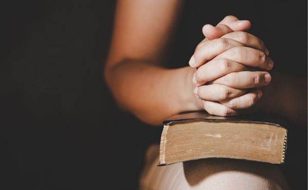 Praying hands on a Bible