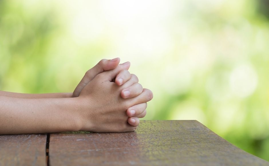 Hands praying on a table outside on a sunny day