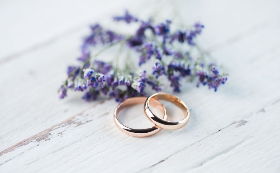 Two wedding rings on a table beside purple flowers