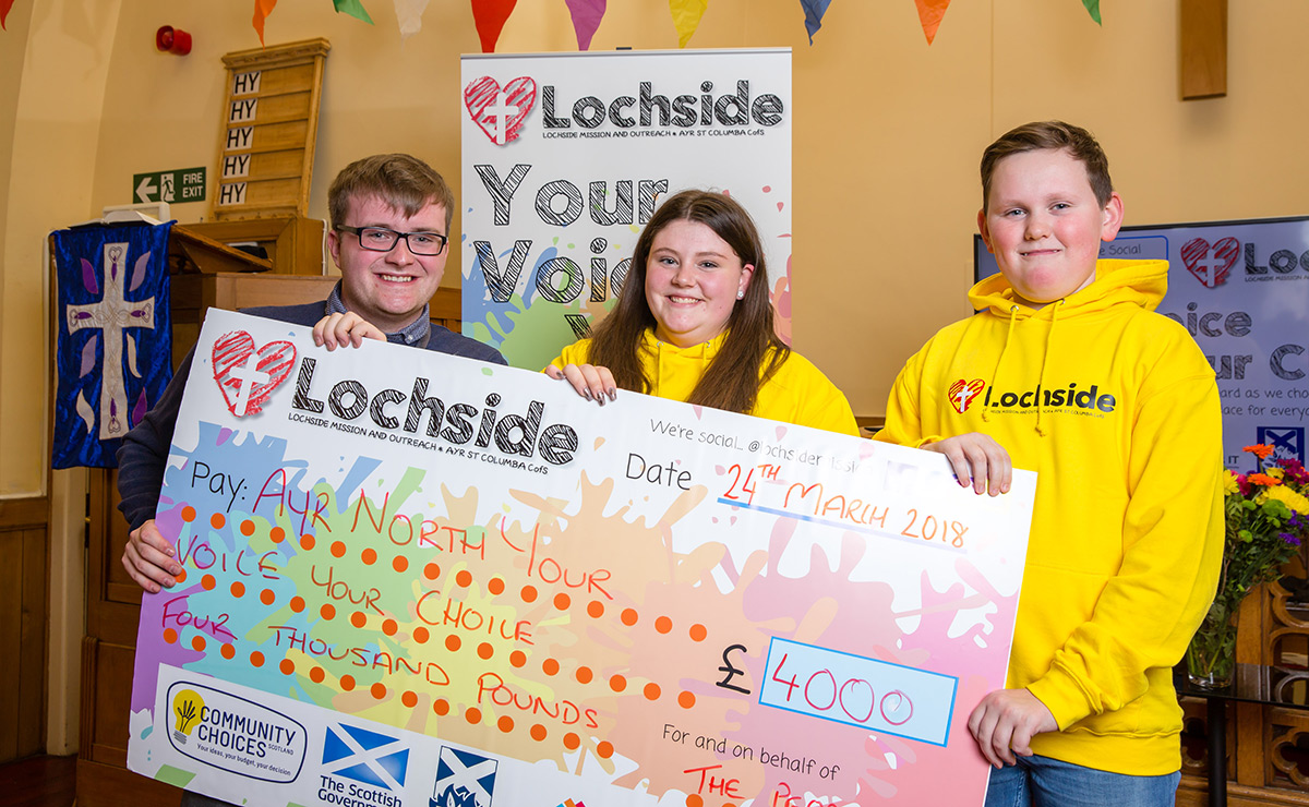 Dylan Harper, Project Leader at Lochside Mission and Outreach, presenting a cheque to Robbie and Megan, who won £750 for their holiday project