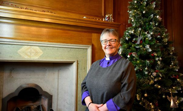 Rt Rev Susan Brown in front of Christmas tree