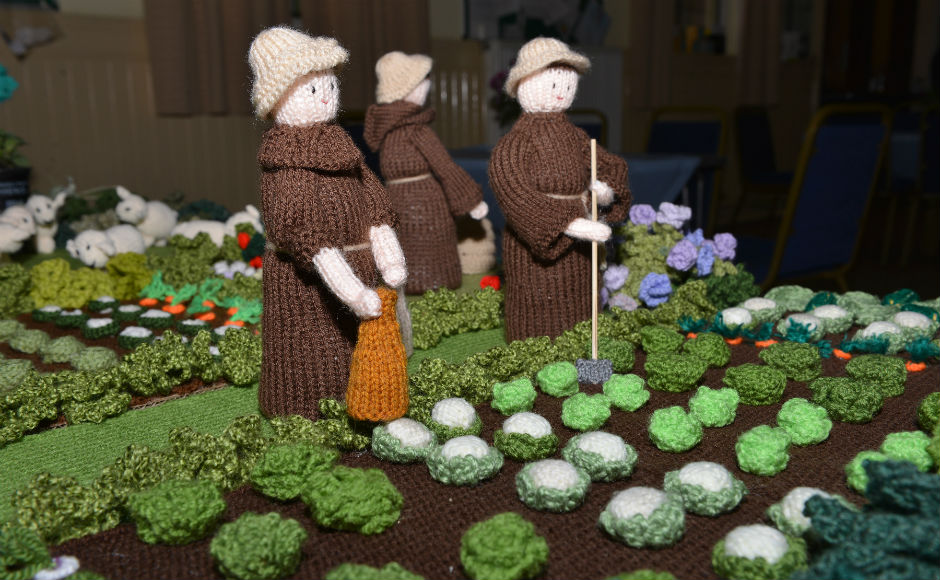Knitted scenes depicting the daily life of monks and pilgrims. this shows the monks gardening.