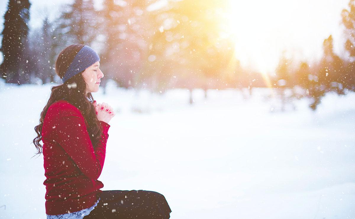 Woman praying in snow