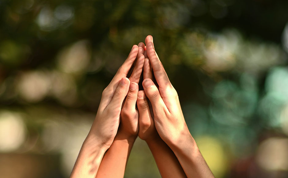 Two pairs of hands raised in prayer