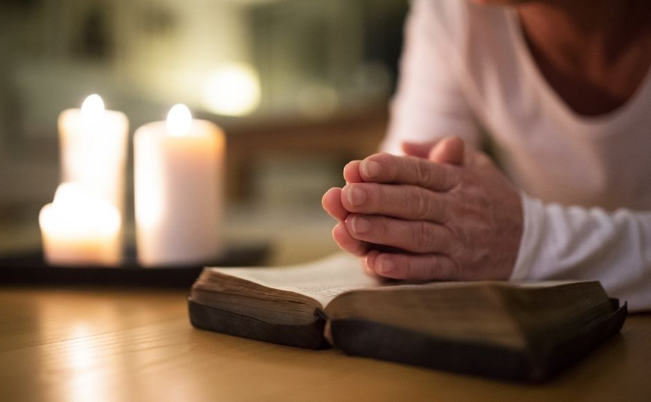 Woman's praying hands on a Bible with candles in the background