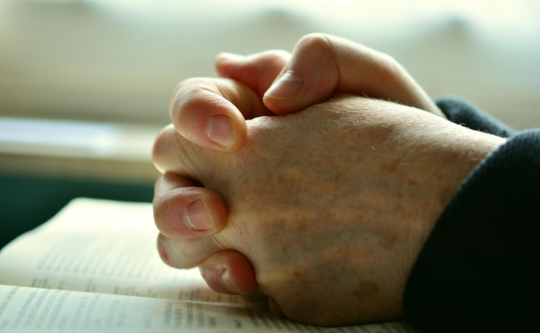 Man's hands praying on a table