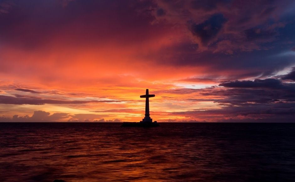Cross standing out at sea at sunset