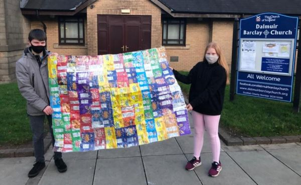 Two people holding up a blanket made from crisp packets