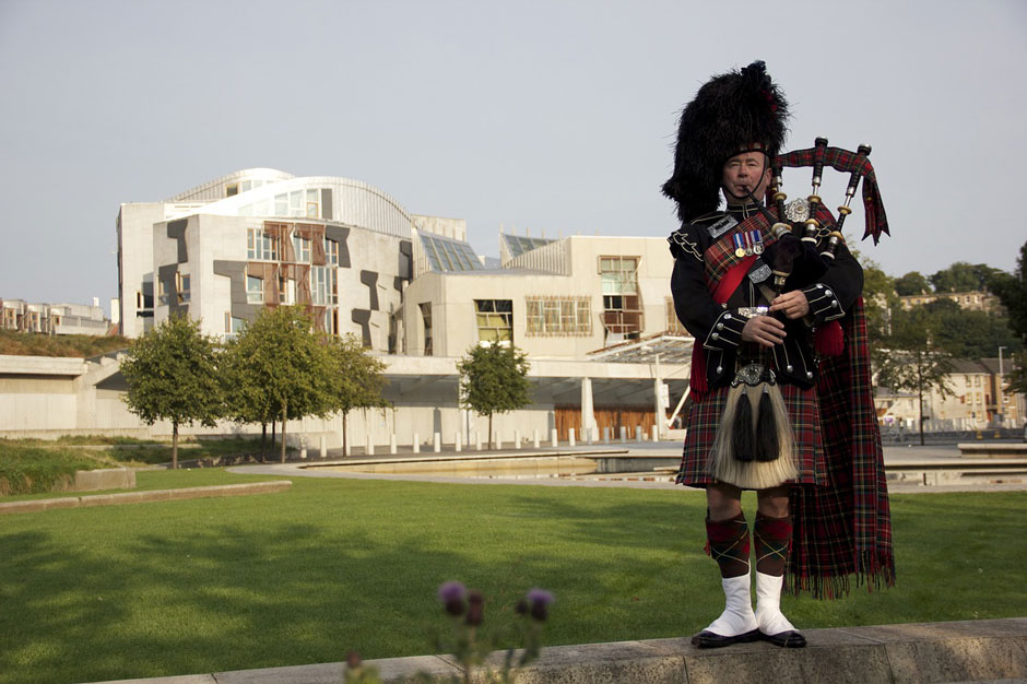 Bagpiper with Scottish Parliament building in the background