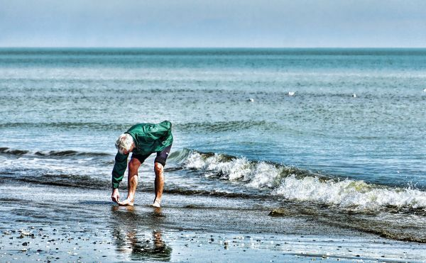 Man picking up pebbles on a beach