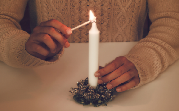 A lady's hands lighting a candle for Advent
