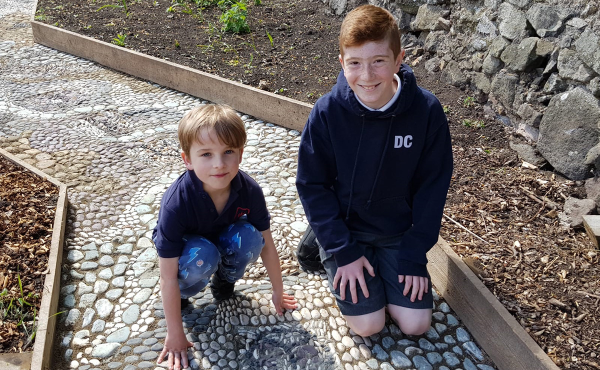 Parsons Green Primary School pupils crouching by the tile they made