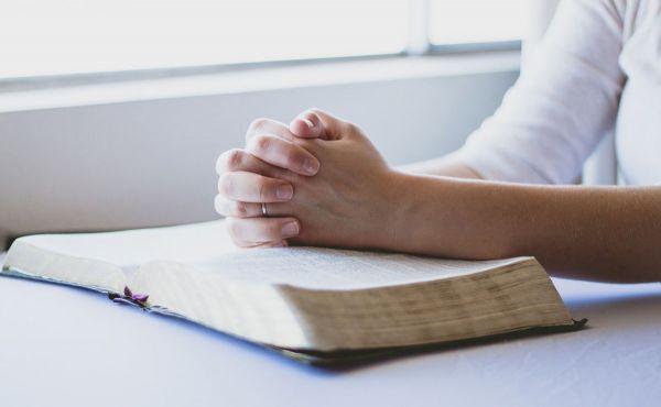 Hands folded over an open bible